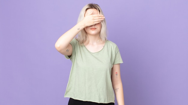 Linda mulher albina cobrindo os olhos com uma das mãos, sentindo-se assustada ou ansiosa, imaginando ou cegamente esperando por uma surpresa