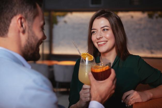 Linda mulher alegre, aproveitando a noite com o namorado no bar de cocktails