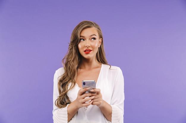 Linda mulher alegre com penteado longo encaracolado usando vestido segurando e digitando no smartphone