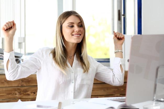 Linda mulher alegre no local de trabalho usando o computador pc