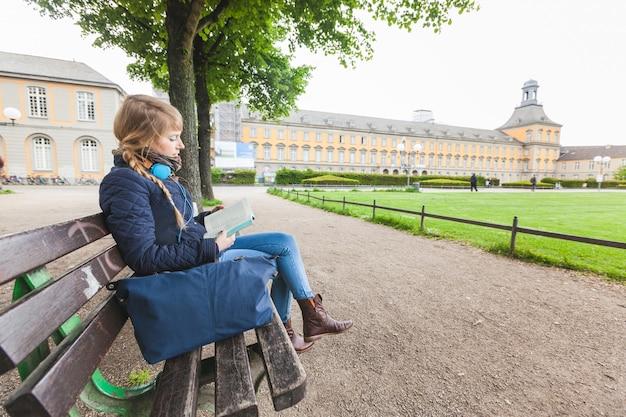 Linda mulher alemã lendo um livro no parque