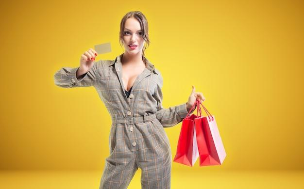Linda mulher alta com pacotes vermelhos nas mãos