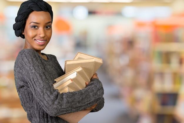 Linda mulher americana afro segurando livros