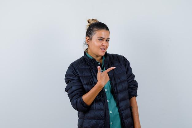 Linda mulher apontando para a direita com o dedo indicador em uma camisa verde, jaqueta preta e olhando confiante, vista frontal.