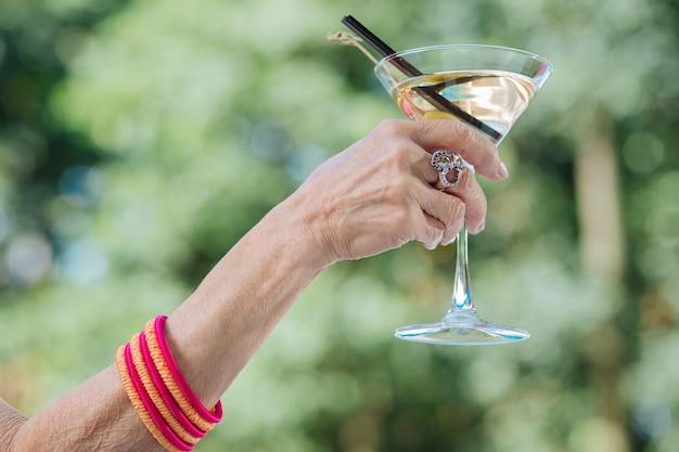 Linda mulher aposentada usando um grande anel elegante e bebendo um coquetel frio de verão perto da piscina