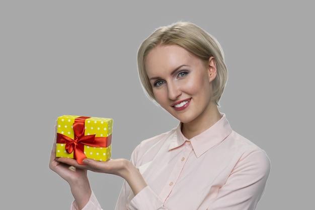 Linda mulher apresentando caixa de presente. mulher bonita caucasiana, segurando uma caixa de presente pequena em fundo cinza.