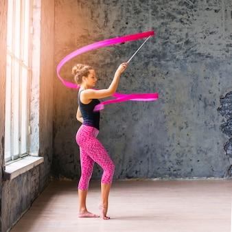 Linda mulher apta dançando com fita rosa
