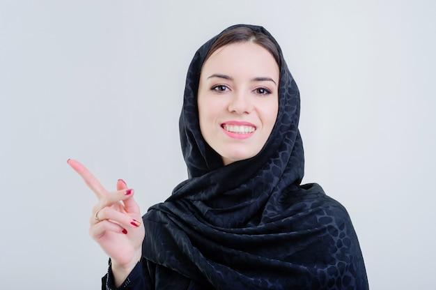 Linda mulher árabe com dedo apontando isolado em fundo cinza.