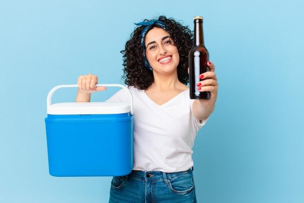 Linda mulher árabe com uma geladeira portátil e uma cerveja