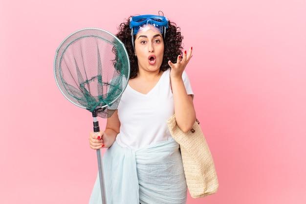 Linda mulher árabe espantada, chocada e atônita com uma surpresa inacreditável com óculos de proteção. conceito de pescador