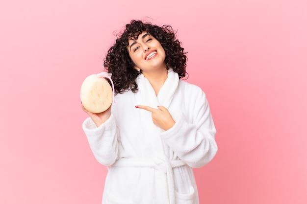 Linda mulher árabe parecendo animada e surpresa, apontando para o lado, vestindo um roupão de banho e segurando uma esponja