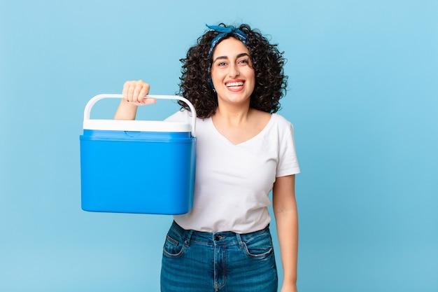 Linda mulher árabe parecendo feliz e agradavelmente surpresa, segurando uma geladeira portátil
