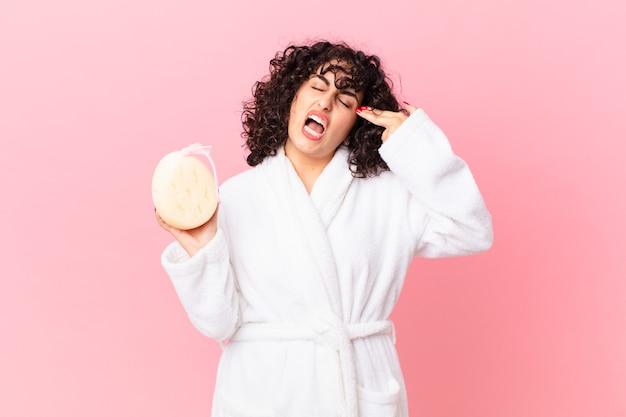 Linda mulher árabe parecendo infeliz e estressada, gesto suicida fazendo sinal de arma, vestindo roupão de banho e segurando uma esponja