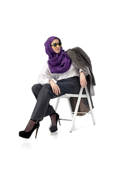 Linda mulher árabe posando em um elegante traje de escritório, isolado no conceito de moda de fundo de estúdio.