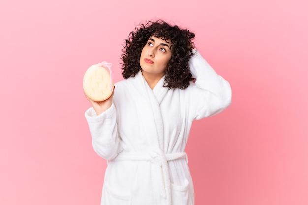 Linda mulher árabe se sentindo perplexa e confusa, coçando a cabeça, vestindo um roupão de banho e segurando uma esponja