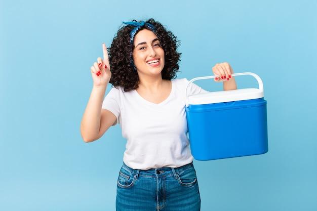 Linda mulher árabe se sentindo um gênio feliz e animado após ter uma ideia e segurando uma geladeira portátil