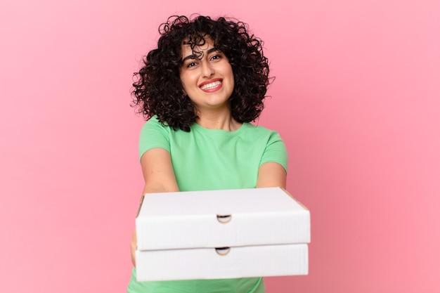 Linda mulher árabe segurando uma caixa de pizza