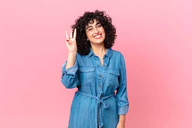 Linda mulher árabe sorrindo e parecendo amigável, mostrando o número três