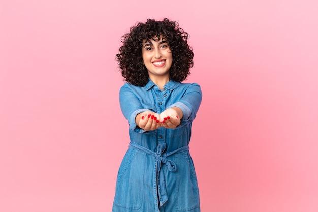 Linda mulher árabe sorrindo feliz com simpatia, oferecendo e mostrando um conceito