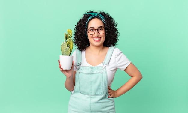 Linda mulher árabe sorrindo feliz com uma mão no quadril e confiante, segurando um cacto em um vaso