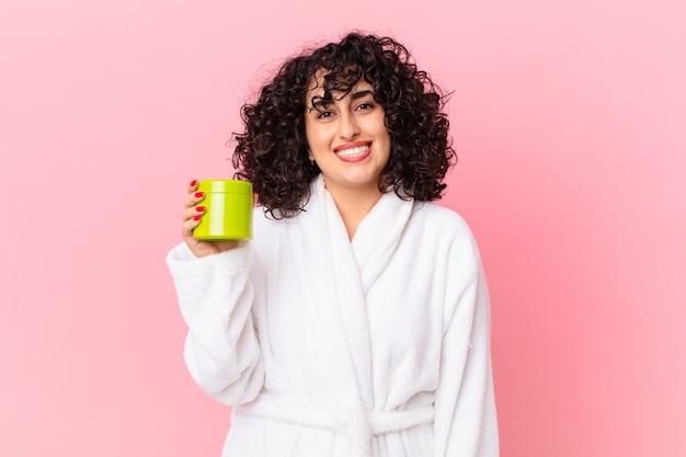 Linda mulher árabe vestindo roupão de banho e segurando um condicionador