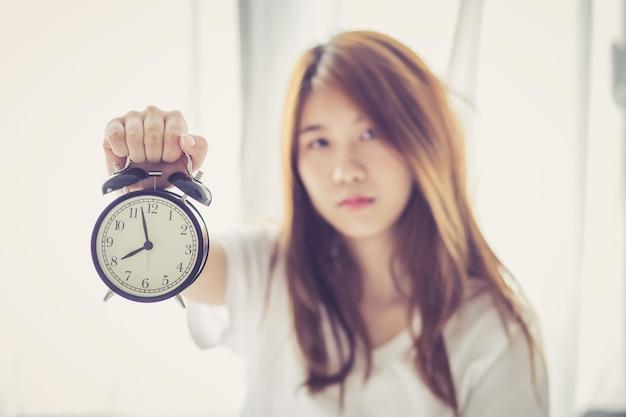 Linda mulher asiática acorda na manhã irritada despertador