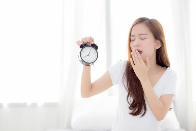 Linda mulher asiática acorda no bocejo de manhã e despertador irritado