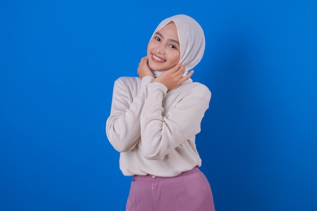 Linda mulher asiática alegre usando a expressão de sorriso de uma camiseta branca com a mão