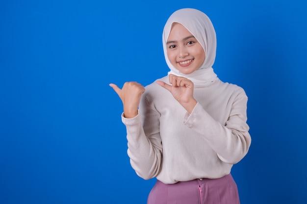 Linda mulher asiática alegre usando a expressão de sorriso de uma camiseta branca com o dedo polegar