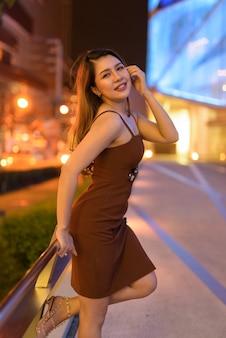 Linda mulher asiática ao ar livre em bangkok, tailândia, à noite