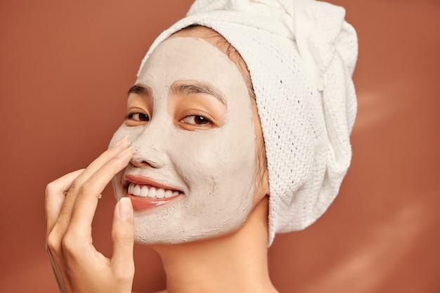 Linda mulher asiática, aplicando a máscara facial no rosto. cuidados com a pele e conceito de tratamento, spa, beleza natural e cosmetologia.