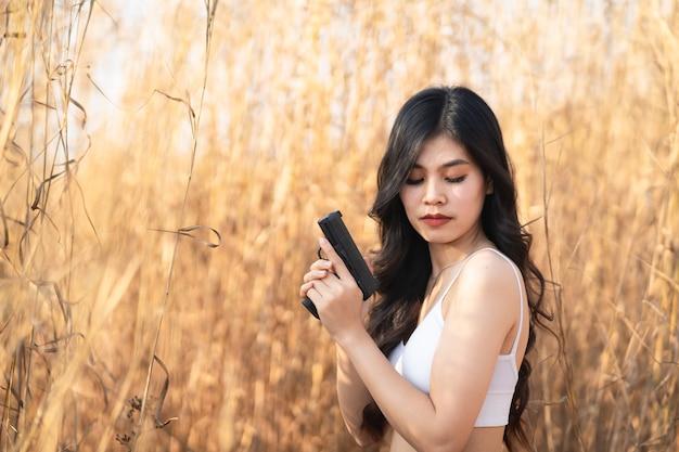Linda mulher asiática apontando a arma na grama seca