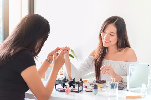 Linda mulher asiática blogger mostrando como unha polonês e usar cosméticos.