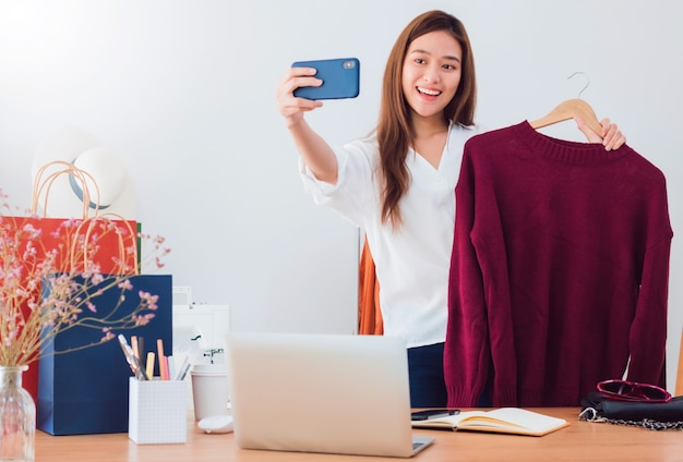 Linda mulher asiática blogueira está mostrando e analisa o produto. na frente da câmera do smartphone em casa.