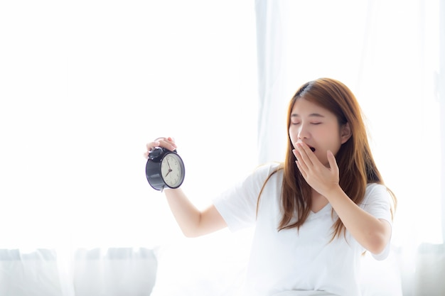 Linda mulher asiática bocejar acordar na manhã irritado despertador