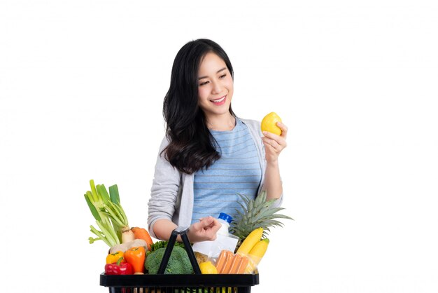 Linda mulher asiática carregando cesta de compras de alimentos e compras, isolados no fundo branco