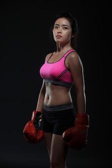Linda mulher asiática com as luvas de boxe vermelhas