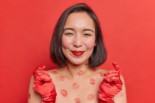 Linda mulher asiática com cabelo escuro curto fica sem camisa, tem vestígios de lábios no corpo, usa luvas vermelhas, batom tem poses de beleza natural dentro de casa