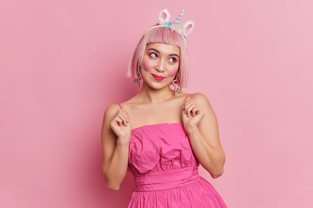 Linda mulher asiática com cabelo rosa concentrado ao lado com expressão sonhadora levantando as mãos