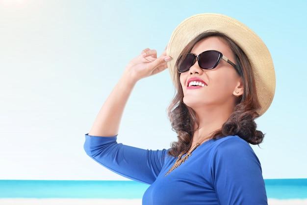 Linda mulher asiática com chapéu nas férias de verão