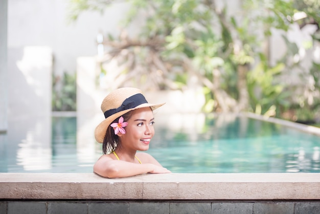 Linda mulher asiática com chapéu relaxante