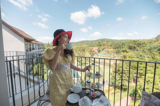 Linda mulher asiática com chapéu, saboreando o chá da tarde e a sobremesa na varanda no jardim inglês.