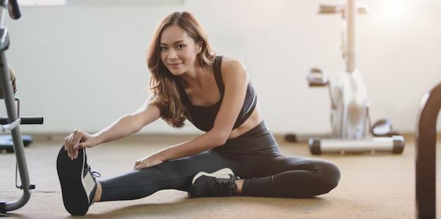 Linda mulher asiática com corpo bronzeado e magro, esticando as pernas antes do exercício na academia