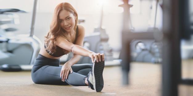 Linda mulher asiática com corpo bronzeado e magro, esticando as pernas antes do exercício