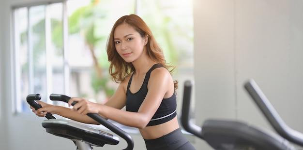 Linda mulher asiática com corpo esbelto, fazendo exercícios cardio na máquina elíptica