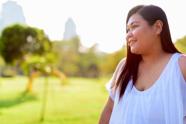 Linda mulher asiática com excesso de peso relaxando no parque