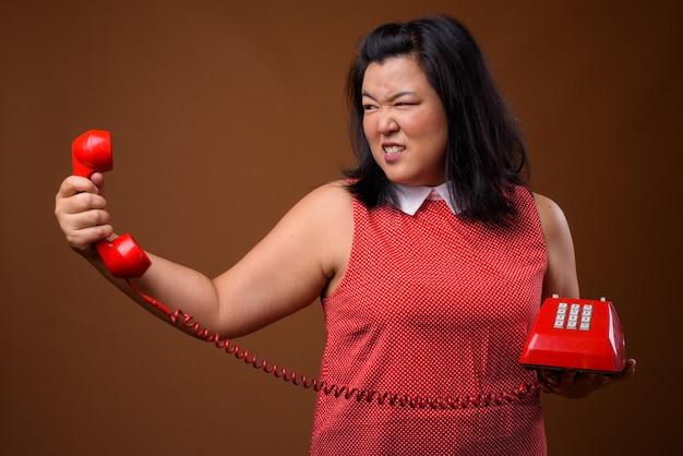 Linda mulher asiática com excesso de peso usando vestido vermelho