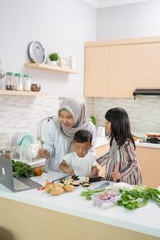 Linda mulher asiática com filha e filho preparando o jantar