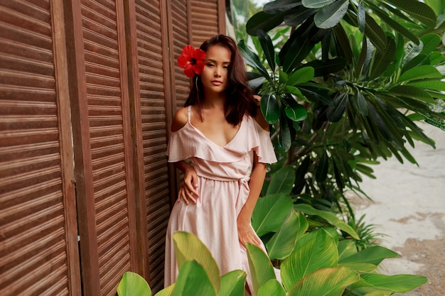 Linda mulher asiática com flor de hibisco nos cabelos posando sobre parede de madeira.