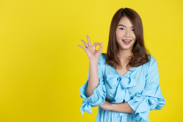 Linda mulher asiática com gesto ok na parede amarela